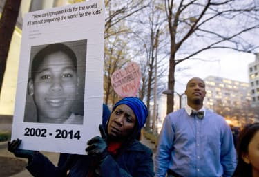 A protester holds up a photo of Tamir Rice.