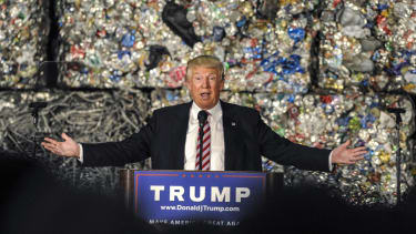 Donald Trump gives a speech in front of a wall of garbage.