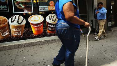 A woman walks past a McDonalds.