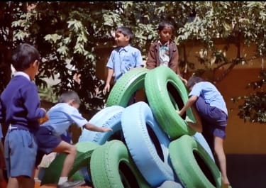 Kids play on their new tire playground equipment.