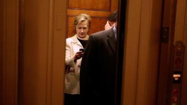 Hillary Clinton checks her BlackBerry