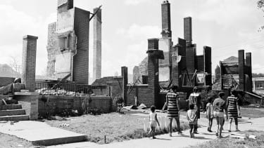 Women and children stroll past the remains of homes