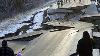 People walk along Vine Road after an earthquake, Friday, Nov. 30, 2018, in Wasilla, Alaska.
