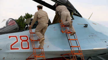 Russia servicemen attend to a plane in Syria.