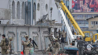 Afghan security officials inspect the damage from a suicide bomb in Kabul