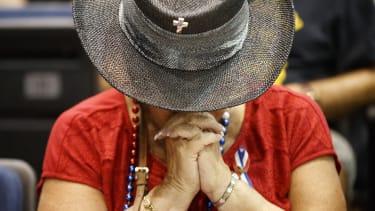 A Trump supporter prays.