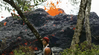 A lava fissure erupts as a resident stands nearby in the aftermath of eruptions from the Kilauea volcano on Hawaii's Big Island, on May 12, 2018 in Pahoa, Hawaii.