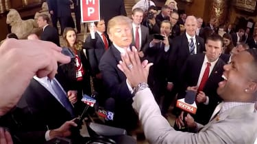 Donald Trump compares hands with an entertainment reporter
