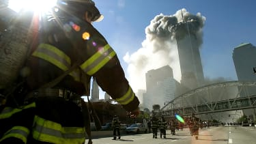 Firefighters race toward the burning twin towers.