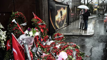 Mourners visit a memorial to the victims of the Reina massacre.