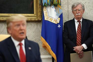 John Bolton looks at Donald Trump.