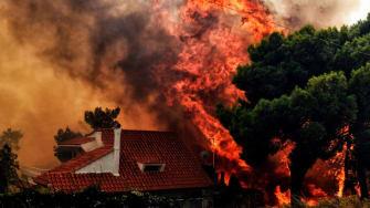 Flames reach a home near Athens, Greece, on Monday.