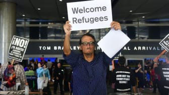 A man holds a sign that reads 'Welcome Refugees' on one side and 'Welcome Muslims' on the other as he walks the International Arrivals section at Los Angeles International Airport on June 29,