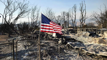 A flag flies above the wreckage left behind from the California wildfire.