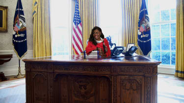 Omarosa Manigault Newman at Oval Office Resolute Desk with a pile of Unhinged memoirs