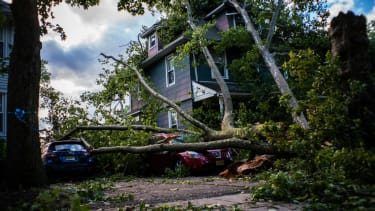 Cars and a house are shown damaged by a fallen tree after Tropical Storm Isaias and its treacherous winds and heavy rain passed through on August 4, 2020 in Bogota, New Jersey.