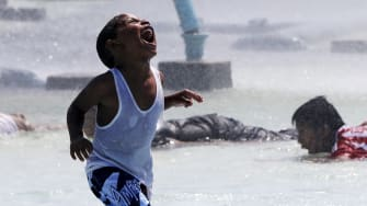 A child plays underneath water cannons in Queens, New York.