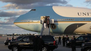 President Donald Trump and his wife Melania Trump walk down the stairs as they arrive with Japanese Prime Minister Shinzo Abe and his wife Akie Abe on Air Force One at the Palm Beach Interna