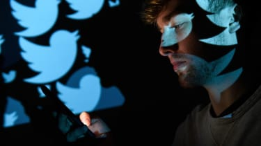 The logo for the Twitter social media network is projected onto a man on August 09, 2017 in London, England