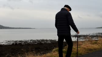 Northern Ireland is seen on the left and the Republic of Ireland is seen on the right with Carlingford Lough in the middle, and an old man walks with a cane along the shore.