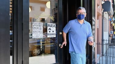 A man wears a mask after getting a haircut.