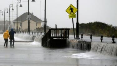People walk across Beach Ave. in Cape May, N.J., as flood waters from Hurricane Sandy rush in on Oct. 29.