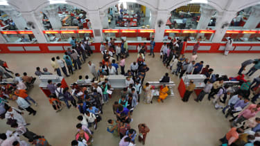 eople wait in lines to deposit and withdraw money inside a post office in Lucknow, India.
