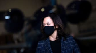 Sen. Kamala Harris (D-CA) wears a facemask as she listens to her running mate speak to reporters at Phoenix Sky Harbor Airport, October 8, 2020, in Phoenix, Arizona.