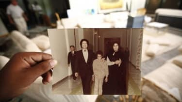 A Libyan shows an old photo of Moammar Gadhafi, his son Seif al Islam and his wife