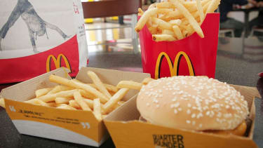 A quarter pounder with cheese sits in front of fries in a McDonald's burger.