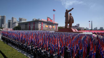 Students march past a balcony from where North Korea's leader Kim Jong Un was watching, during a mass rally on Kim Il Sung square in Pyongyang on September 9, 2018.