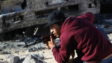 A rebel fighter ducks from incoming fire on a street in downtown Misrata, Libya: The EU may send up to 1,000 soldiers to ensure humanitarian aid reaches this rebel stronghold.