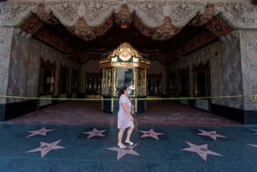A woman walks in front of the El Capitan Theater in Hollywood.