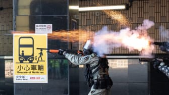 Riot police in Hong Kong fire tear gas canisters at protesters.