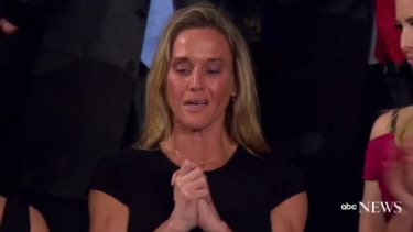 """The widow of Navy Seal William """"Ryan"""" Owens listens to applause for her late husband."""