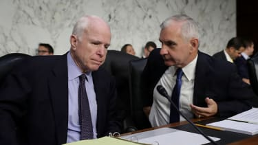Committee chairman Sen. John McCain  listens to Sen. Jack Reed before a  Senate Armed Services Committee hearing.