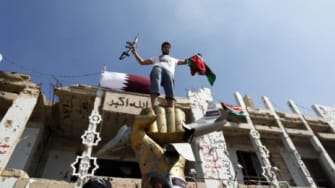 A Libyan fighter takes a souvenir photo as rebels flush out pro-Gadhafi forces in Tripoli: With victory near, critics say the NATO-led effort still failed the rebel fighters.