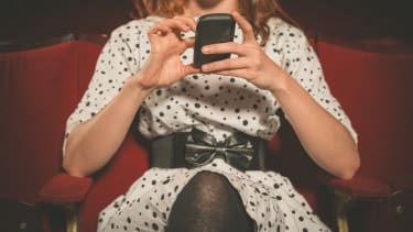 Woman using phone in theater.