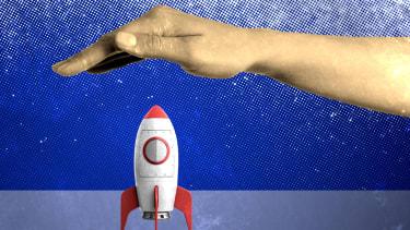 A hand blocking a rocket ship.