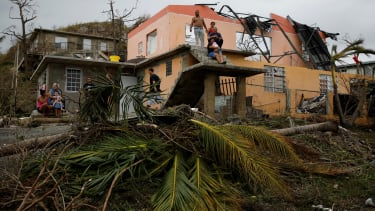 Residents sit outside a damaged home after Hurricane Maria.