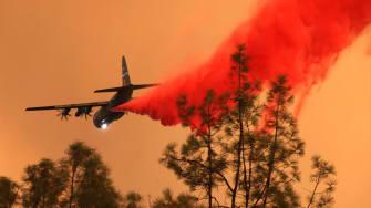 An airplane drops fire retardant.