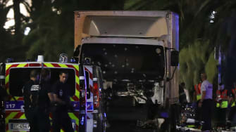 Police officers and rescued workers stand near a van that ploughed into a crowd leaving a fireworks display in the French Riviera town of Nice.