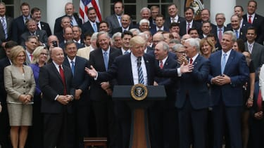 President Trump speaks with House Republicans behind him.