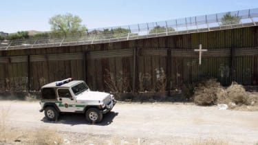 A border patrol agent drives past the U.S.-Mexico border wall.