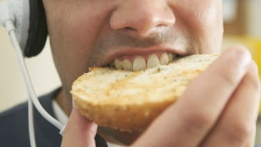A man eating a bagel and listening to podcasts