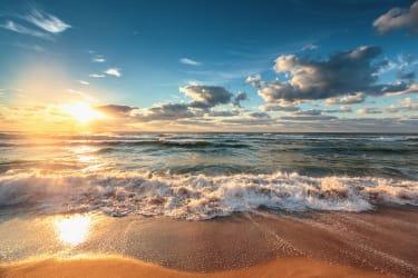 The sun rises over the ocean.