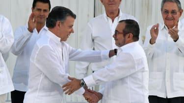 Colombian President Juan Manuel Santos, left, and the head of the FARC guerrilla Timoleon Jimenez, aka Timochenko, shake hands in September.
