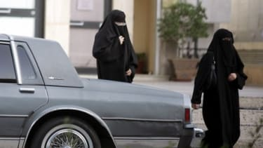 Two Saudi women walk past a parked car: A female Saudi activist, Manal al-Sharif, defied the conservative Muslim kingdom's ban on women driving and spent five days in jail as a result.
