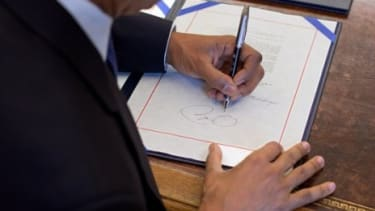 President Obama, who's left-handed, signs papers in the Oval Office: Studies suggest that lefties are more restrained decision makers than their right-handed counterparts.