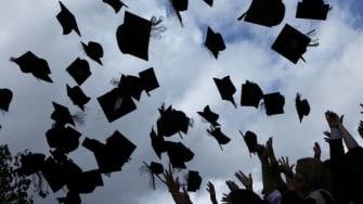 Graduates throw their caps.